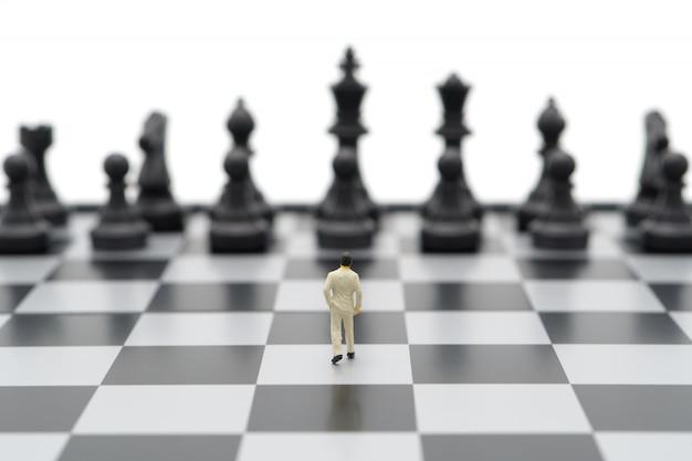 Миниатюрные бизнесмены стоя на шахматной доске с шахматной фигурой на спине. Premium Фотографии