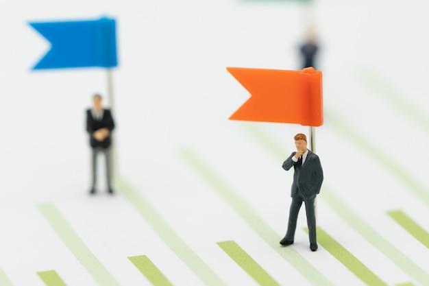 ミニチュアのビジネスマンの立場投資分析または投資セールスランキング Premium写真
