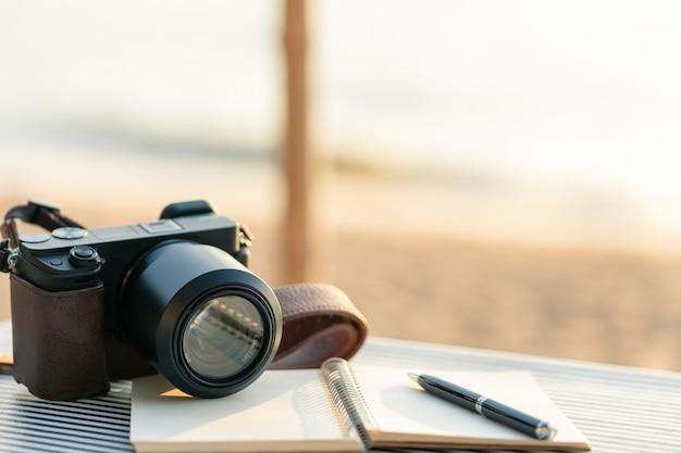ペンが付いている日記浜辺のテーブルに置かれて Premium写真