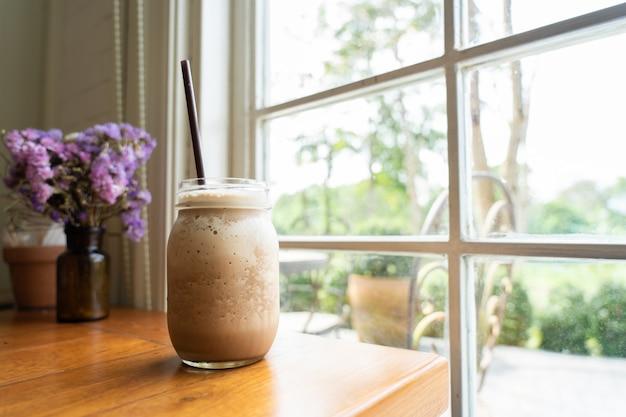 背の高い透明なガラスにココア飲料を混ぜ合わせた、窓際に置いた爽やかな Premium写真