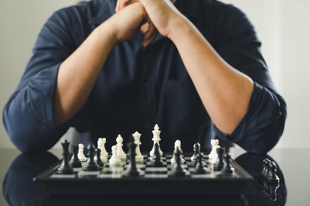 チェス盤にキングチェスを保持している実業家が配置されます。 Premium写真