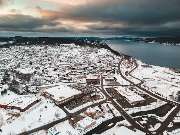黄金の時間の間に曇り空の下で水の体の近くの雪に覆われた住宅の航空写真 無料写真