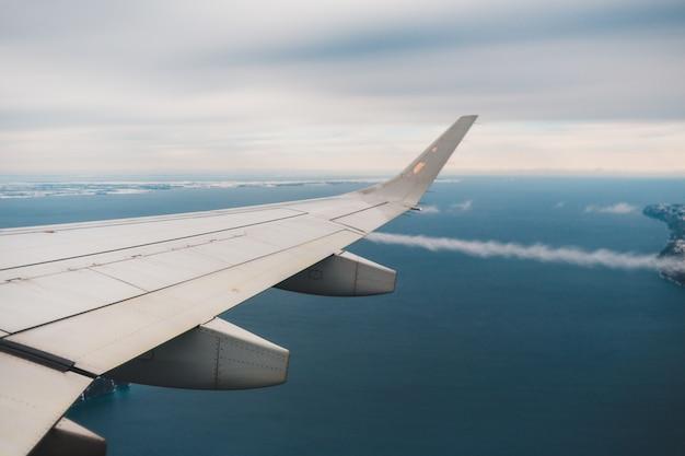 昼間の青い空に白い飛行機の翼 無料写真