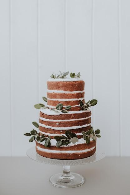 白い木製の背景にユーカリで飾られた美しい素朴なウエディングケーキ 無料写真
