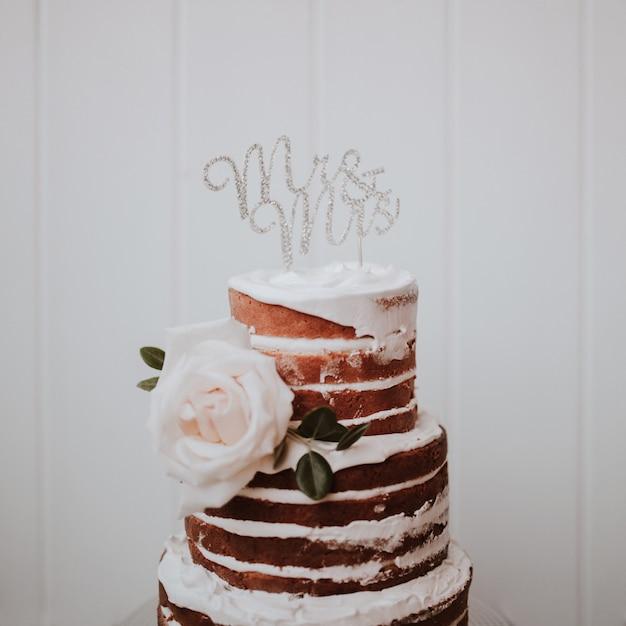 白い木製の背景に白いバラで飾られた美しいウェディングケーキ 無料写真
