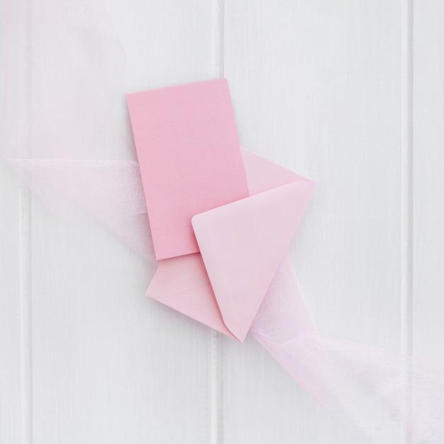 白い木製の背景上の封筒とピンクのグリーティングカード 無料写真