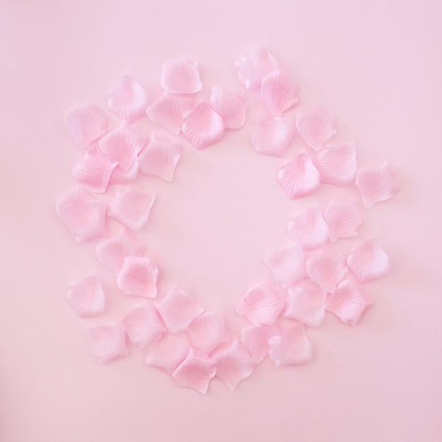 ピンクの背景にピンクのバラの花びらで作られたフレーム 無料写真