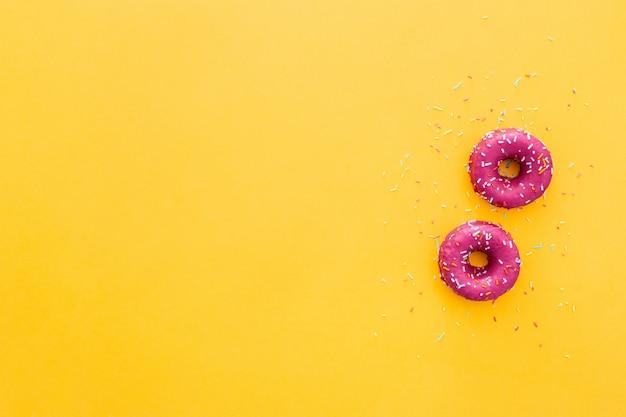 黄色の背景にピンクのアイシングでドーナツのトップビュー 無料写真