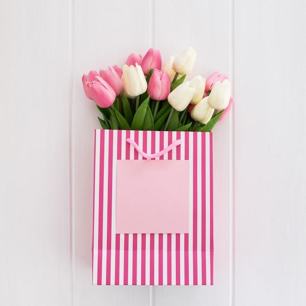 クールなピンクの買い物袋にピンクと白のチューリップの束 無料写真