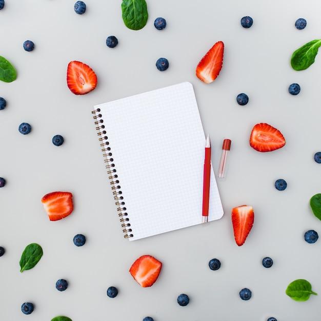 空のノートブックとイチゴとブルーベリーの灰色の背景 無料写真