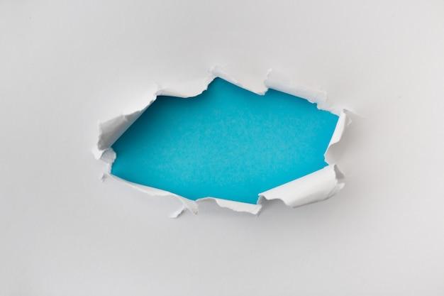 白い色の穴を引き裂かれ、青い背景と紙の破れた。テキストのコピースペース領域と引き裂かれた紙のテクスチャ 無料写真