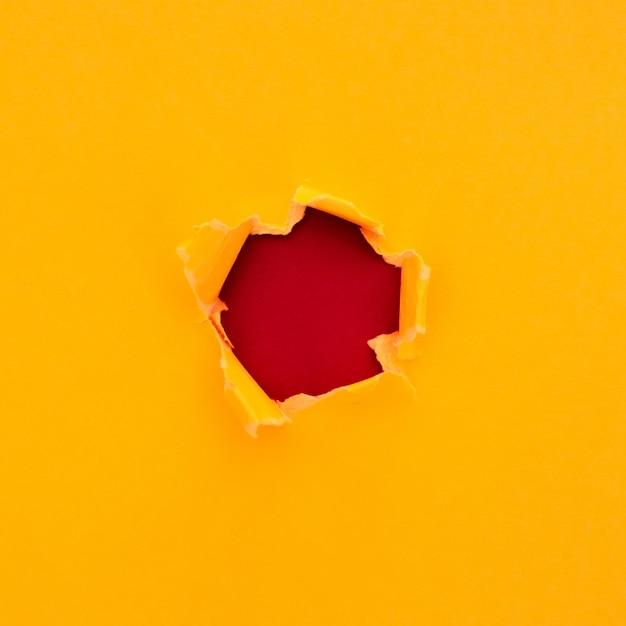 赤い段ボールの背景にテキスト用のスペースと引き裂かれた黄色い紙 無料写真