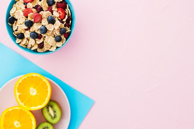 夏の朝食の組成。シリアル、パステル調のピンクの背景にフルーツ。 無料写真