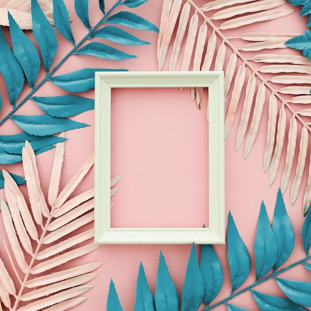 ピンクの背景に白いフレームと熱帯の青とピンクのヤシの葉 無料写真