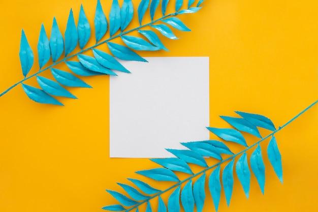 黄色の背景に青い葉を持つ空白の紙 無料写真