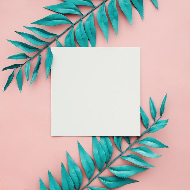 空白のフレームとピンクの背景に美しい青いボーダーの葉 無料写真