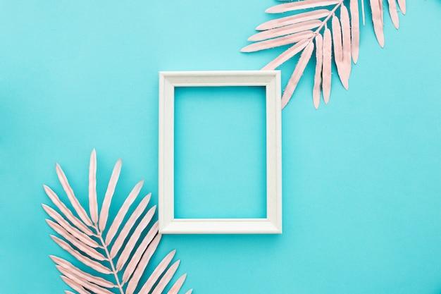 ピンクのヤシの葉と青い背景に素敵な白いフレーム 無料写真