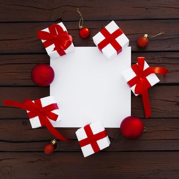 クリスマスボックスとコピースペースを持つ空白の紙 無料写真