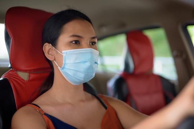 Молодая азиатская женщина в маске для защиты от вспышки вируса короны во время вождения автомобиля Premium Фотографии