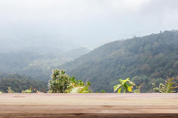 木製のテーブルライトブラウン色の山と霧の背景。モンタージュ商品展示用。 Premium写真