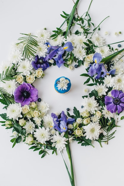 花と果物の白い背景の上の春のカップケーキ Premium写真