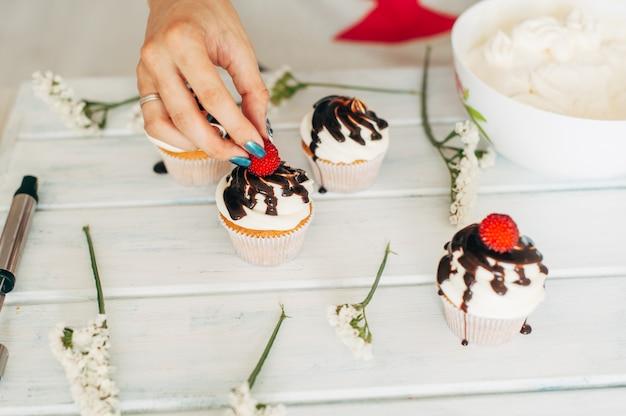 若い女の子が新鮮なベリーと花でカップケーキを飾る Premium写真