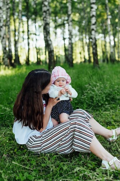 草の上に座っている赤ちゃんと面白いママ Premium写真