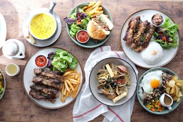 Различный тип еды на деревянном столе Premium Фотографии