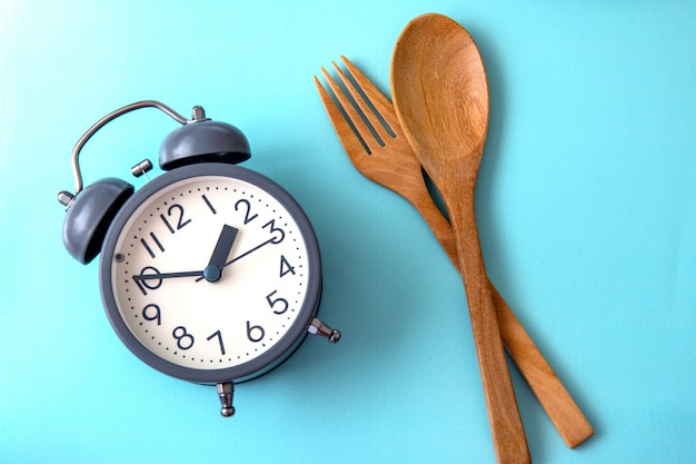 体重を減らす時間、食事のコントロール、またはダイエットの概念、青色の背景に健康的なツールのコンセプト装飾が施された目覚まし時計 Premium写真