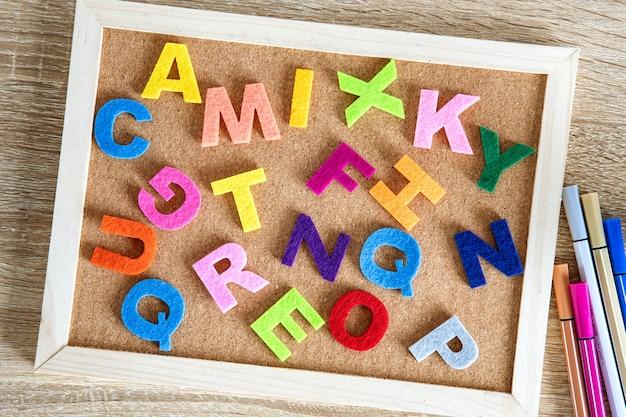 ピンボードの背景にカラフルな英語のアルファベット Premium写真