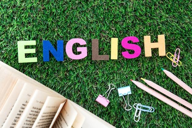 緑の芝生の庭、英語学習の概念上のカラフルな英語単語キューブ Premium写真