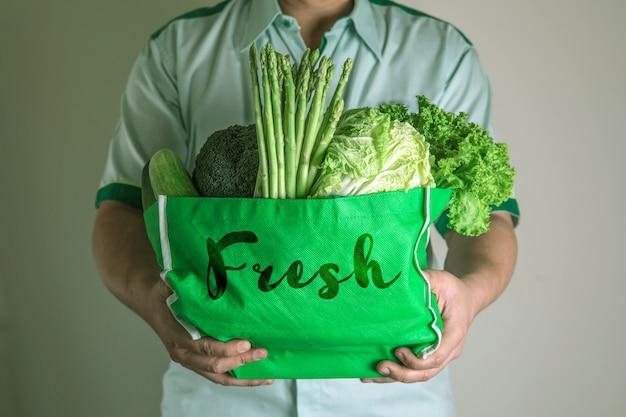 Закройте вверх по руке держа зеленую продуктовую сумку смешанных органических зеленых овощей, здорового органического зеленого магазина еды и диетпитания здравоохранения терапию питания Premium Фотографии