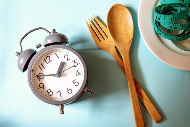 体重、食事のコントロール、食事の時間、青の健康的なツールコンセプト装飾と目覚まし時計を失う時間 Premium写真