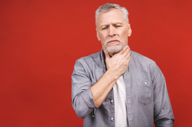 分離されたカジュアルな服を着て、喉の痛みと首に触れている年配の男性。飲み込みにくい。 Premium写真