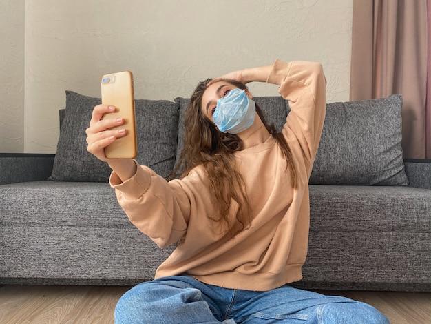 医療マスクの魅力的な女の子は、コロナウイルスのパンデミックによる自宅での自己分離で座っているスマートフォンで自分撮りを取る Premium写真