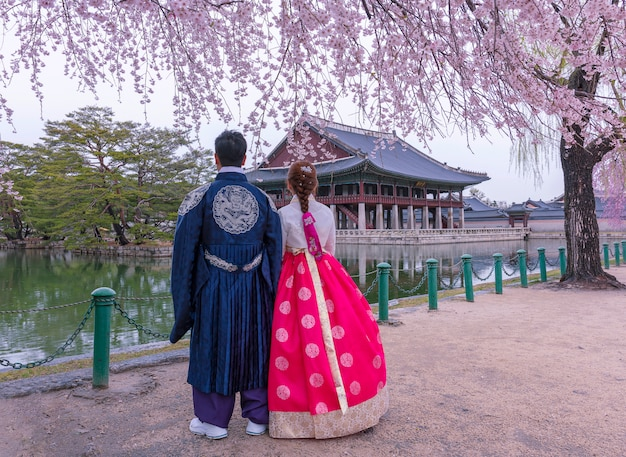 Дворец кёнбоккун с корейским национальным платьем и цветением вишни весной, сеул, южная корея. Premium Фотографии