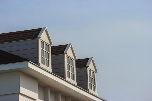 Взгляд перспективы современной стены дома дизайна двускатной крыши с предпосылкой неба вечера. Premium Фотографии