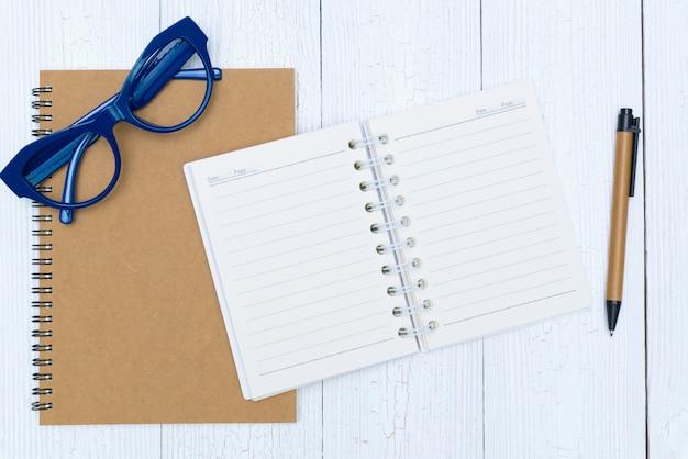 男の手がペンでノート用紙の空白のページに書く Premium写真