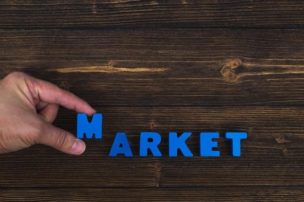 Рукой и пальцем упорядочить текстовые буквы слова маркет Premium Фотографии
