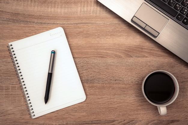 メモと作業テーブルの上のコーヒーカップ Premium写真