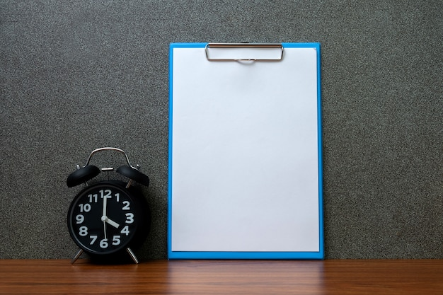 クリップボードと空白のホワイトペーパーと黒のビンテージの目覚まし時計 Premium写真