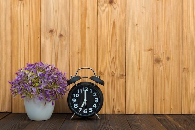 木の上のビンテージの目覚まし時計と小さな木 Premium写真