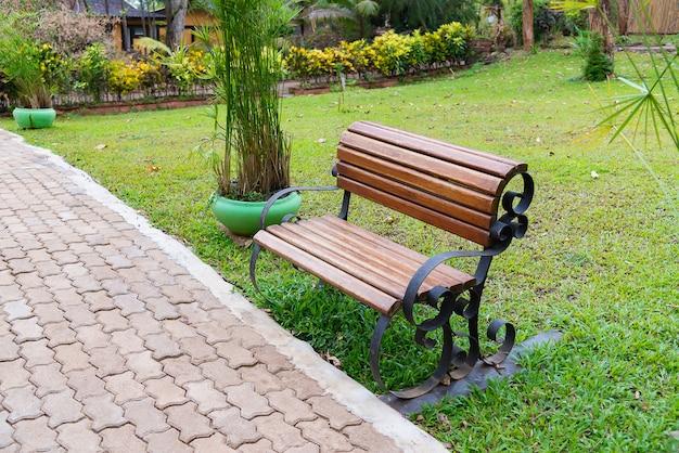 牧草地と屋外の庭や公園の木製ベンチ。 Premium写真
