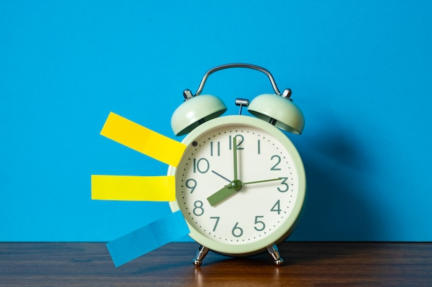 メモ紙付箋とビンテージの目覚まし時計のテーブル Premium写真