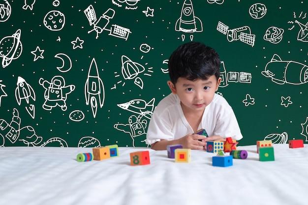 Азиатский ребенок играет игрушку с наукой и космическими приключениями, рисованной фон Premium Фотографии