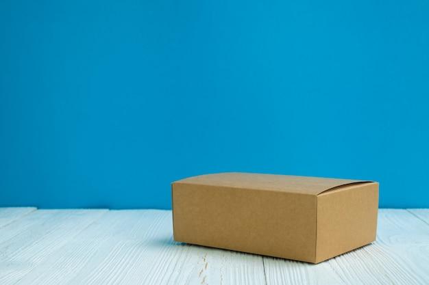 空のパッケージ茶色の段ボール箱や水色の壁の背景を持つ明るい白い木製のテーブルの上のトレイ。 Premium写真