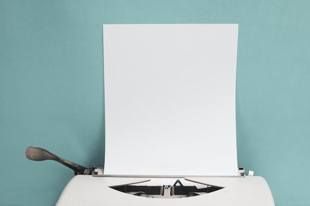 コピースペースと白い木のテーブル前面の青い壁の背景に空白の紙シートとレトロタイプライター。 Premium写真