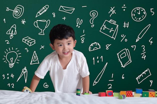 文房具についての彼の想像力で遊ぶことによって学ぶアジアの子供は、学習のための学校目的活動を供給します Premium写真