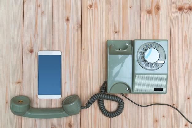 Ретро роторный телефон и новый сотовый телефон или смартфон на дереве Premium Фотографии