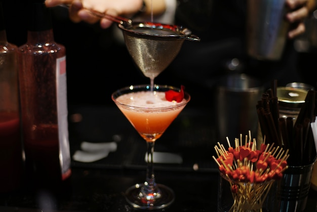 バーテンダーがナイトクラブのバーカウンターでオレンジ色のカクテルにおいしい液体を注ぐ。 Premium写真